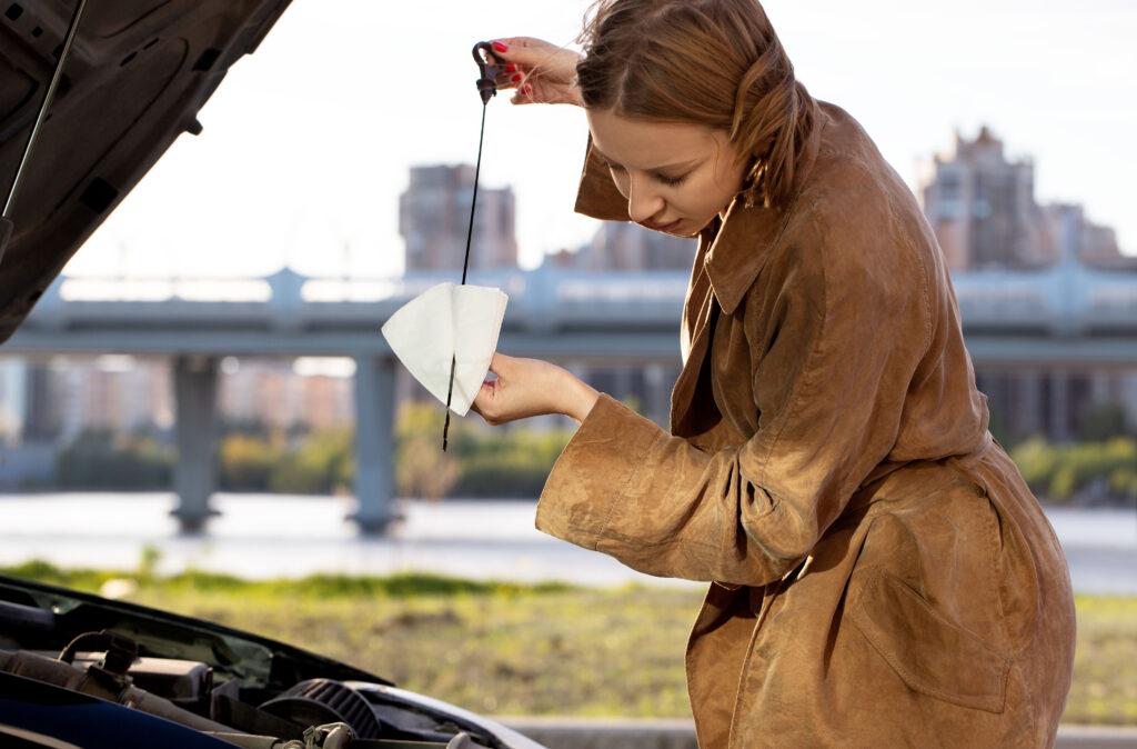 stock car info Confident caucasian woman driver checking oil level in car engine