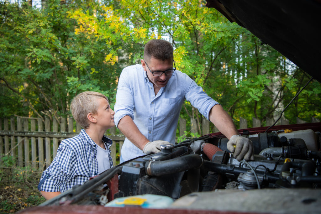 Stock Car Info Young father teaching his son to change motor oil in family car.